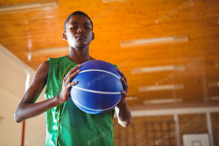 Low angle portrait teenager holding ball