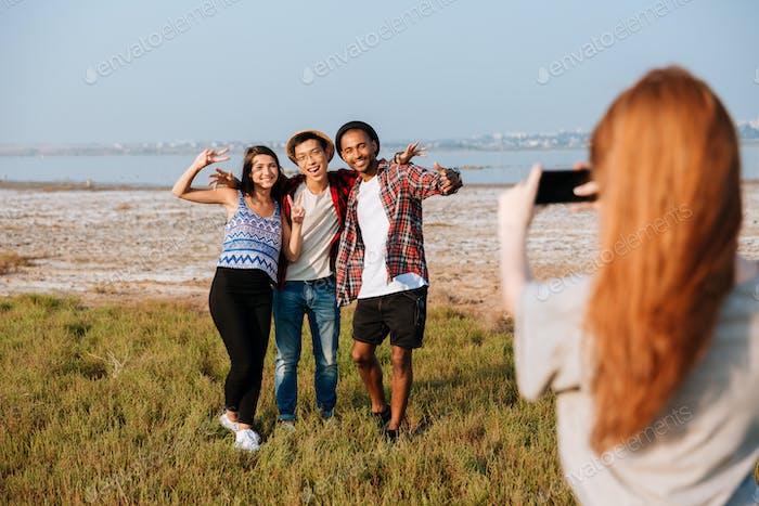 Mujer Encantador fotos de sus Amigos con el teléfono Móvil al aire libre