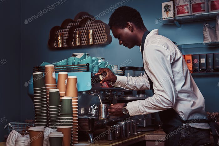 Side View of African American barista in white shirt and apron making coffee with a coffee machine.