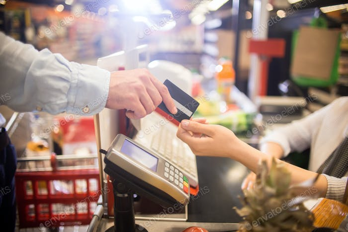 Man Paying with Credit Card in Supermarket