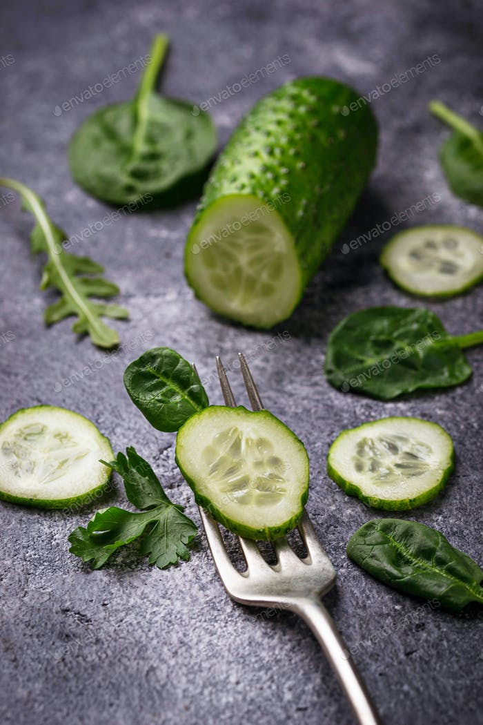 Sliced cucumber on fork and spinach leaves.