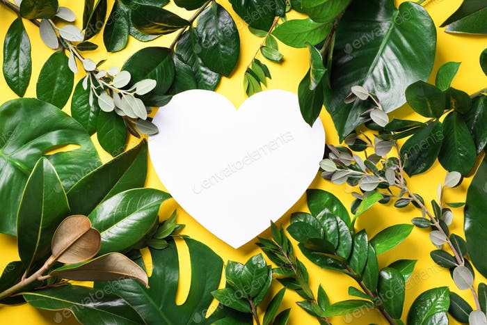 Tropical nature background with green leaves and white heart shaped paper for copy space. Top view