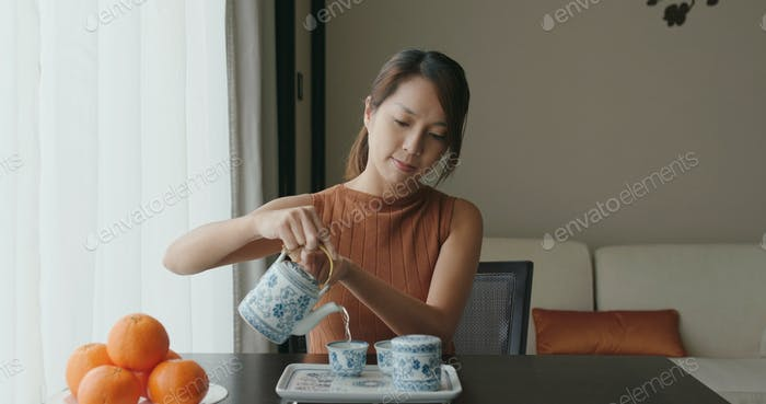 Woman offering Chinese tea ceremony at home