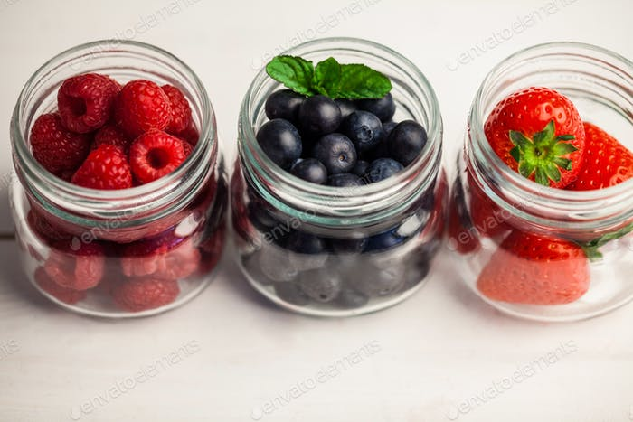 Glass jars of fresh berries on wooden table