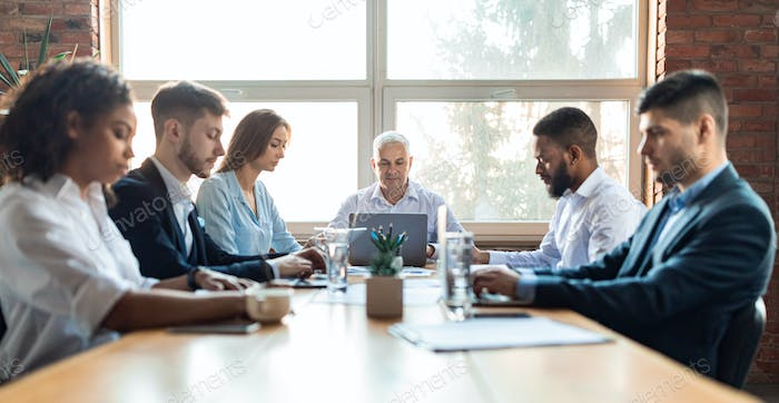 Colleagues Working During Corporate Meeting Sitting At Desk In Office