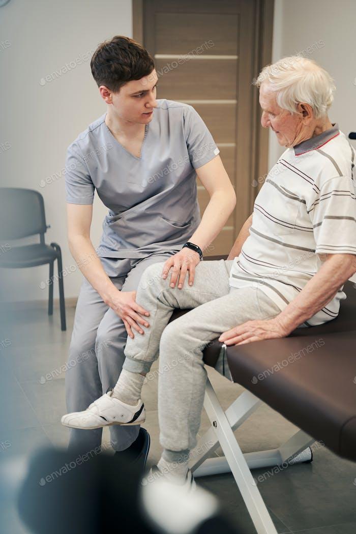 Worried doctor feeling senior citizen leg with hands