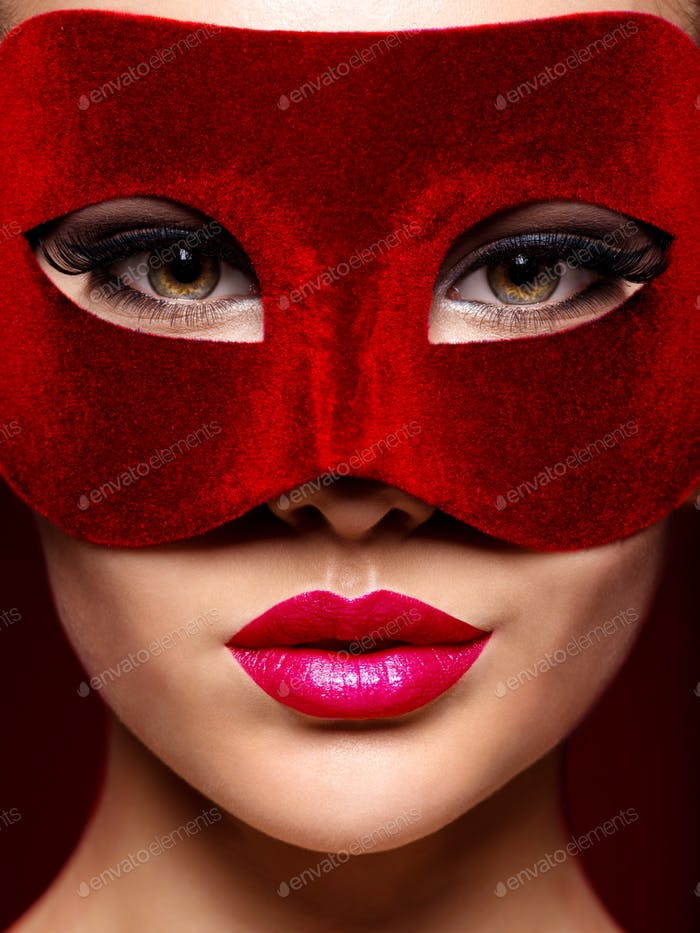 Woman in red  theatre mask on face with violet lips