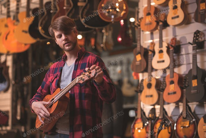 A young man playing the ukulele in a store