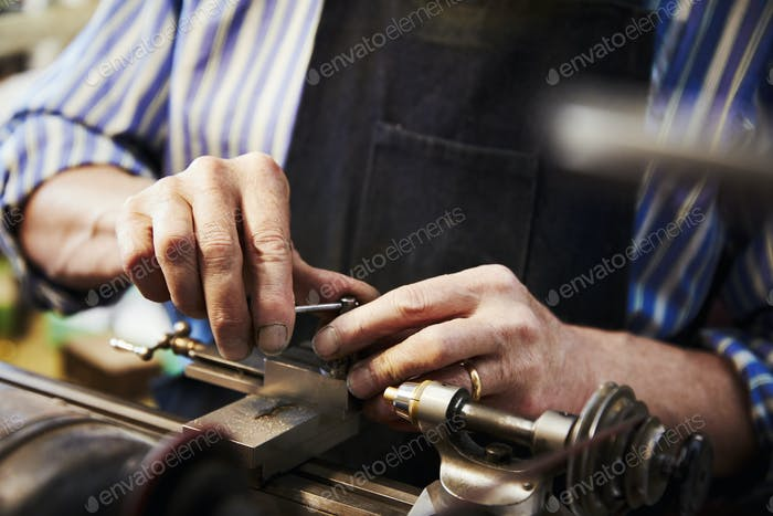 A clock maker and repairer working on the small parts of a clock using a clamp on a workbench.