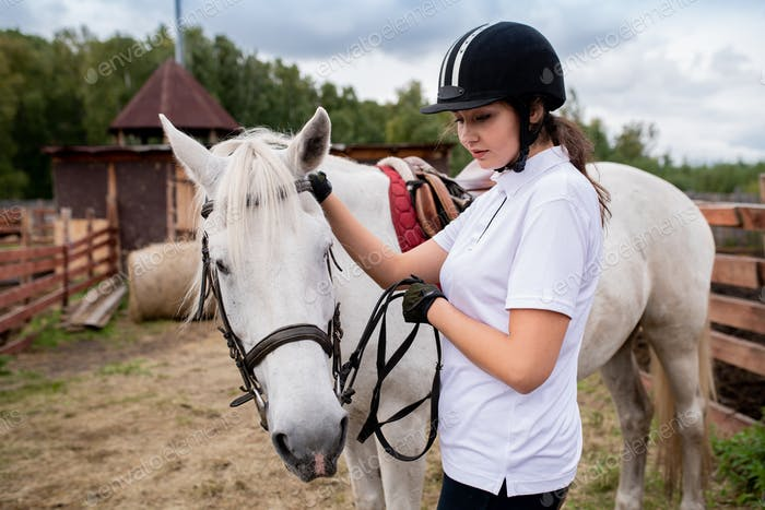 Active girl in equestrian helmet and her racehorse moving down field