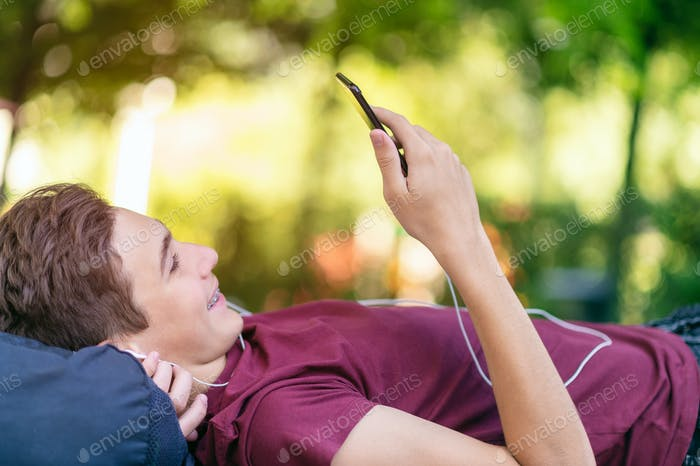 Happy teenage boy is using mobile phone, outdoors.