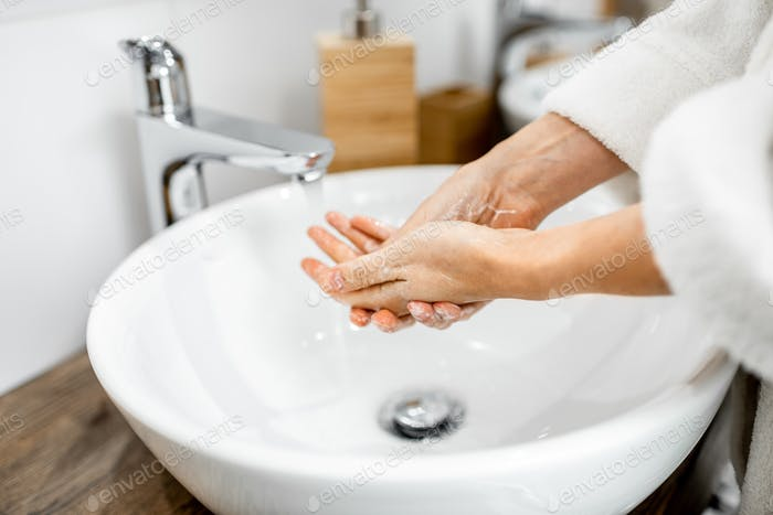 Woman washing hands at the bathroom