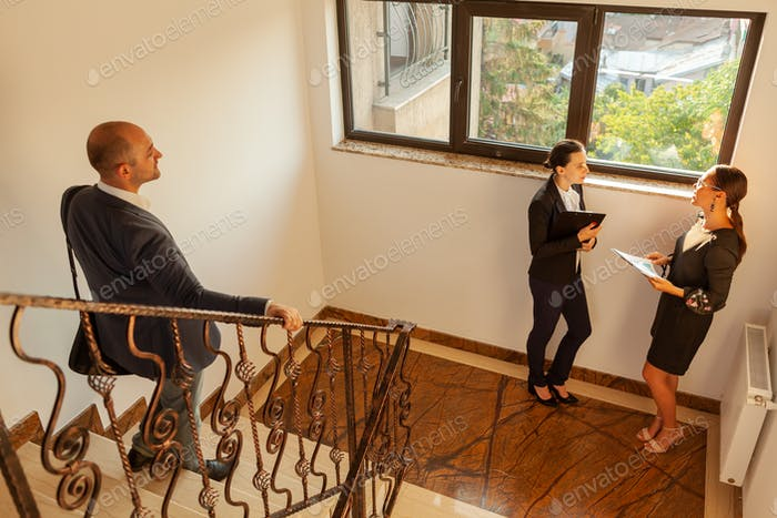 Businessman going downstairs meeting coworkers on office staircase