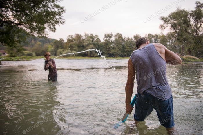 jóvenes hombres tener divertido con agua armas