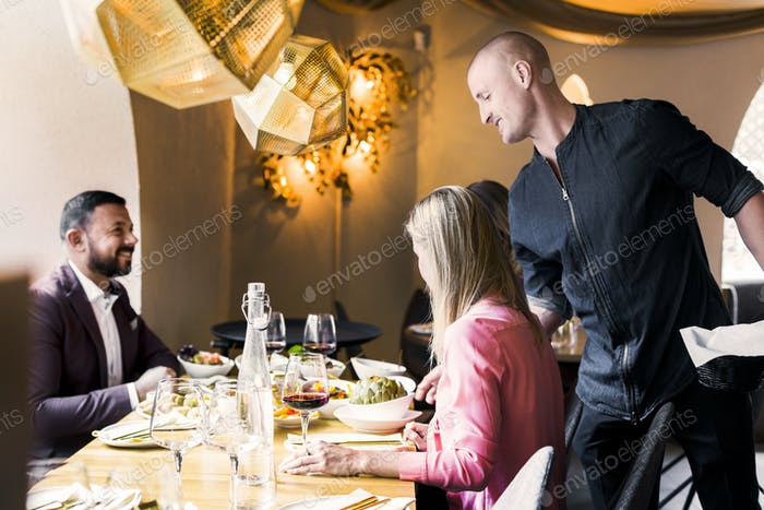 Waiter serving meze to couple sitting at table in restaurant