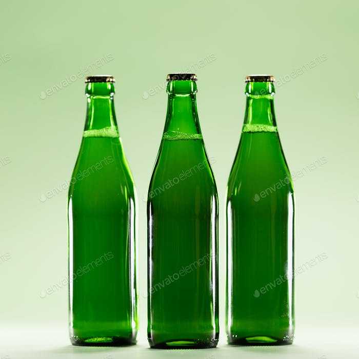 Three green bottles on a light green background.