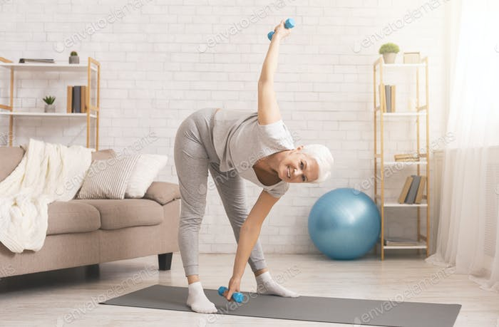 Senior lady exercising with dumbbells at home