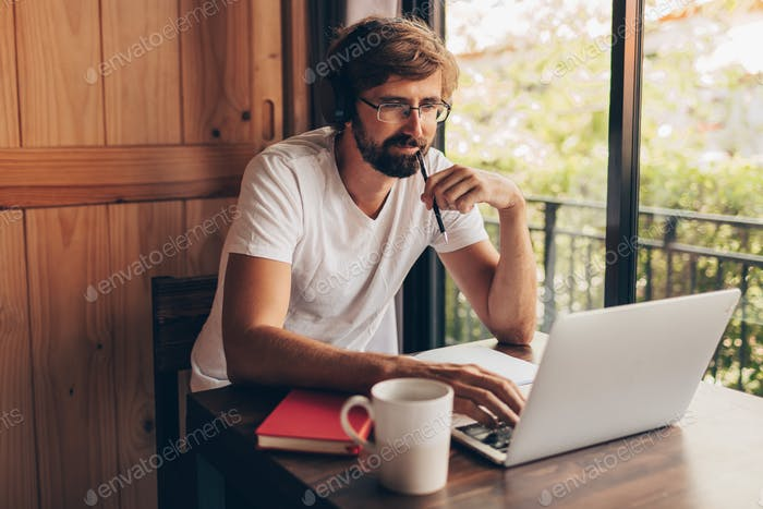 Pensive man with beard using laptop, making notes and watching online courses  or working at home.