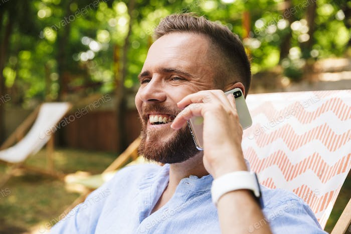 Happy young bearded man outdoors talking by phone.