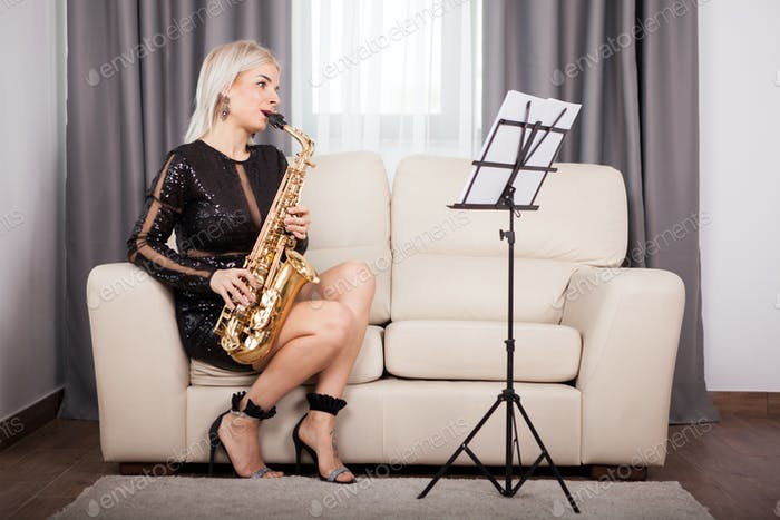 Beautiful saxophonist girl playing at her musical instrument in