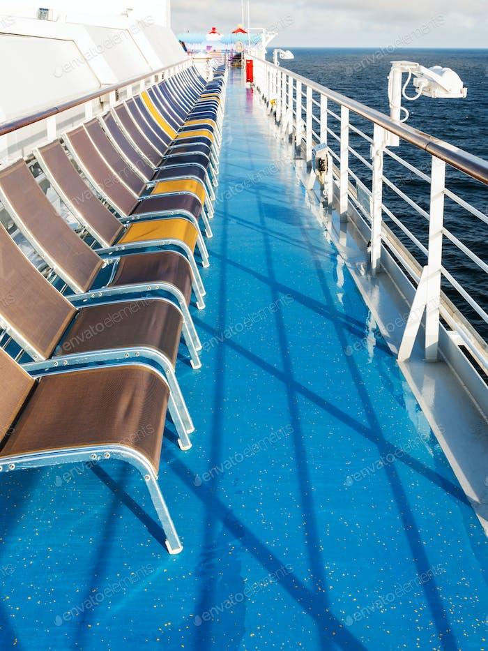 row of empty sunbathing chairs on deck
