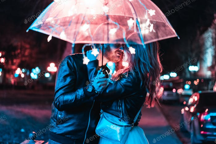 Guy and girl kissing under an umbrella