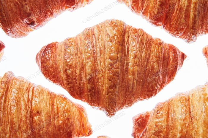 Close up pattern fresh french croissants on a white background