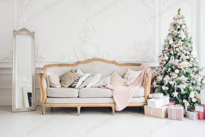Christmas tree with a white sofa in a white room.