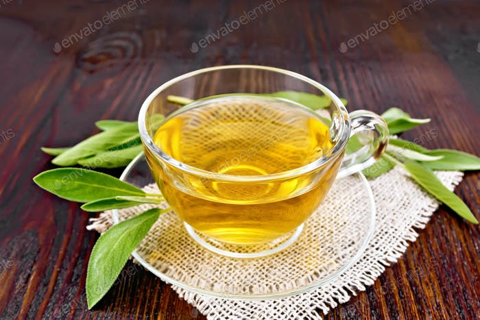 Tea herbal with sage in glass cup on dark wooden board