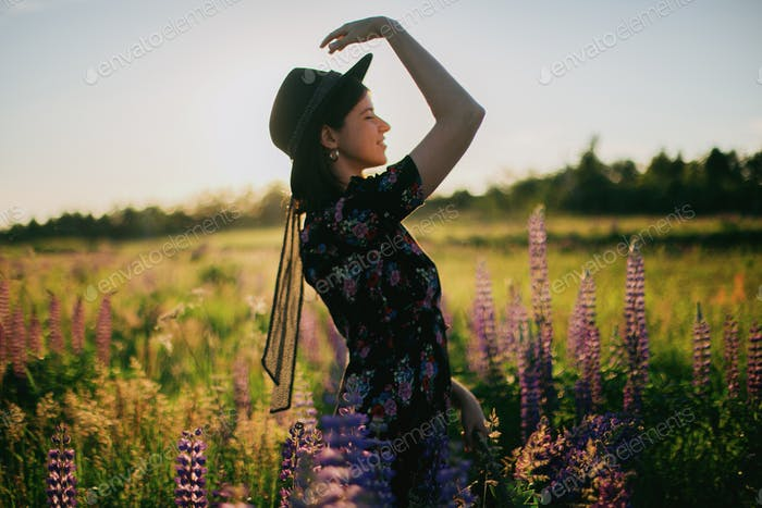 Blurred image of beautiful woman in hat posing among lupine flowers in sunset light in field