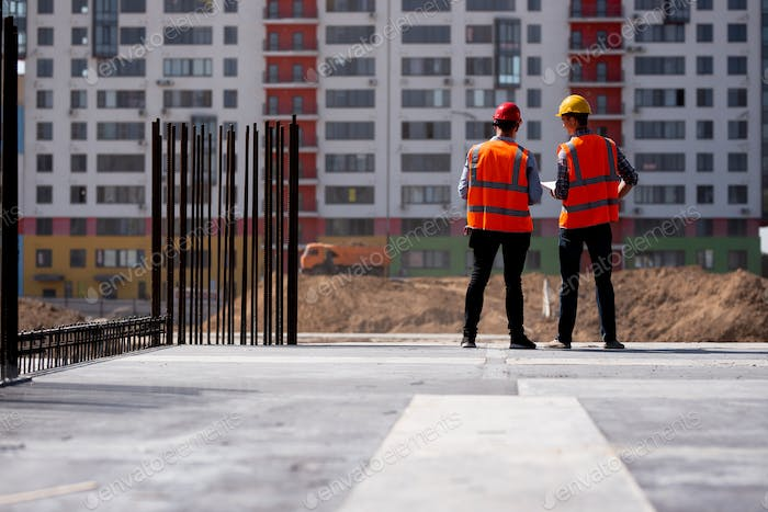 Two civil engineers dressed in orange work vests and helmets talk about the construction process on