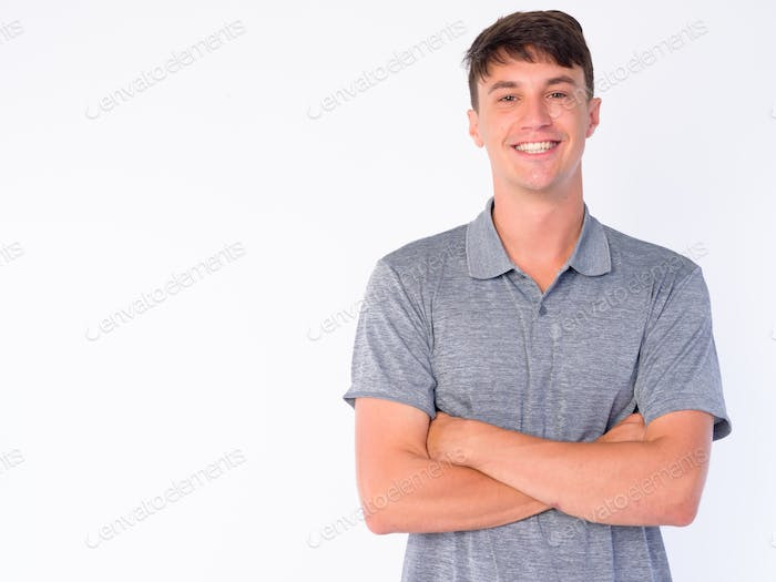 Portrait of happy young handsome man smiling with arms crossed