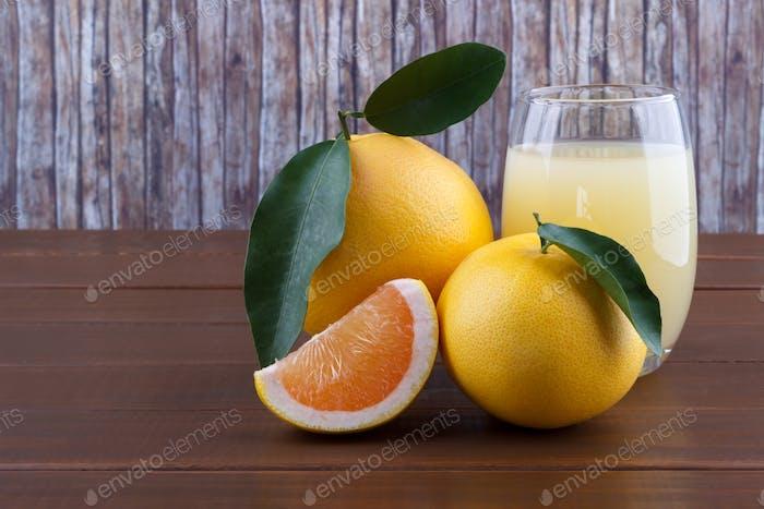 Pomelo y jugo sobre mesa de De madera