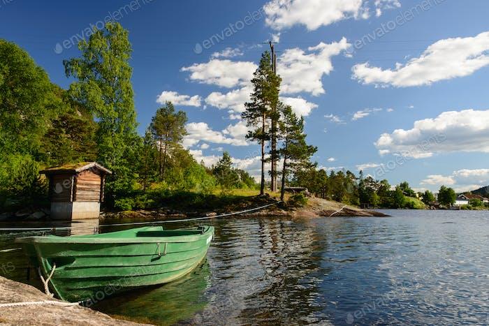 Grünes Boot auf einem See in einer Landschaft in Norwegen