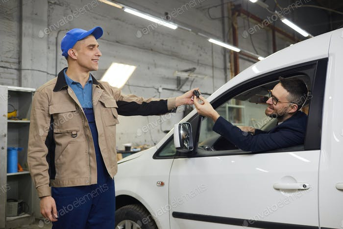 Repairman Giving Keys To Happy Client