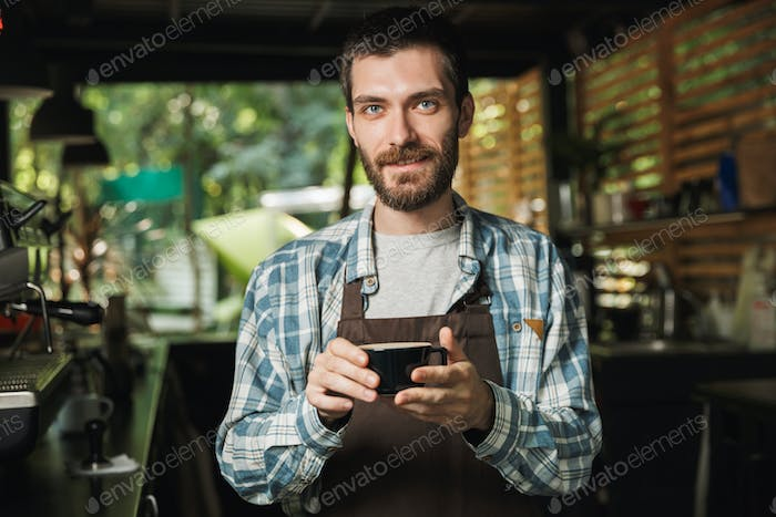 Image of kind barista man making coffee while working in cafe or