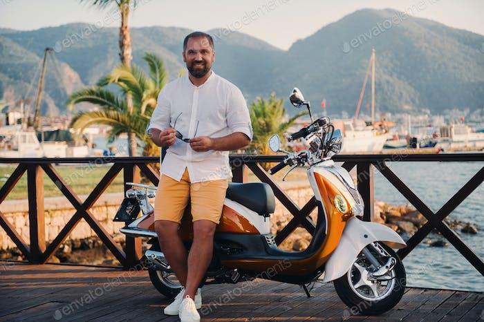 Porträt eines freien glücklichen Mann mit Roller in der Nähe des Meeres.Erholung, Reisen auf einem Roller