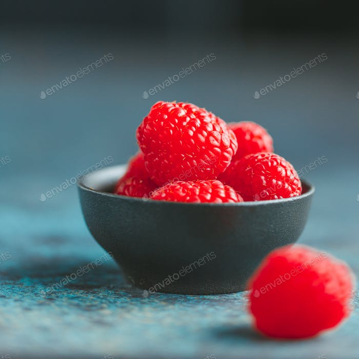 Fresh ripe raspberries in a small black bowl on a textured blue table. Macro photography.