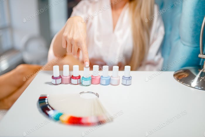 Female customer choosing nail varnish, beauty shop