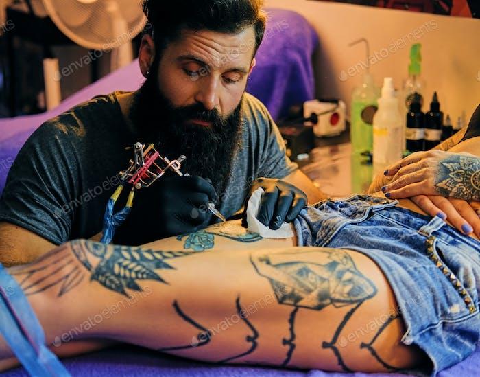 Бородатый татуировщик делает татуировку на ноге женщины в чернильном салоне.