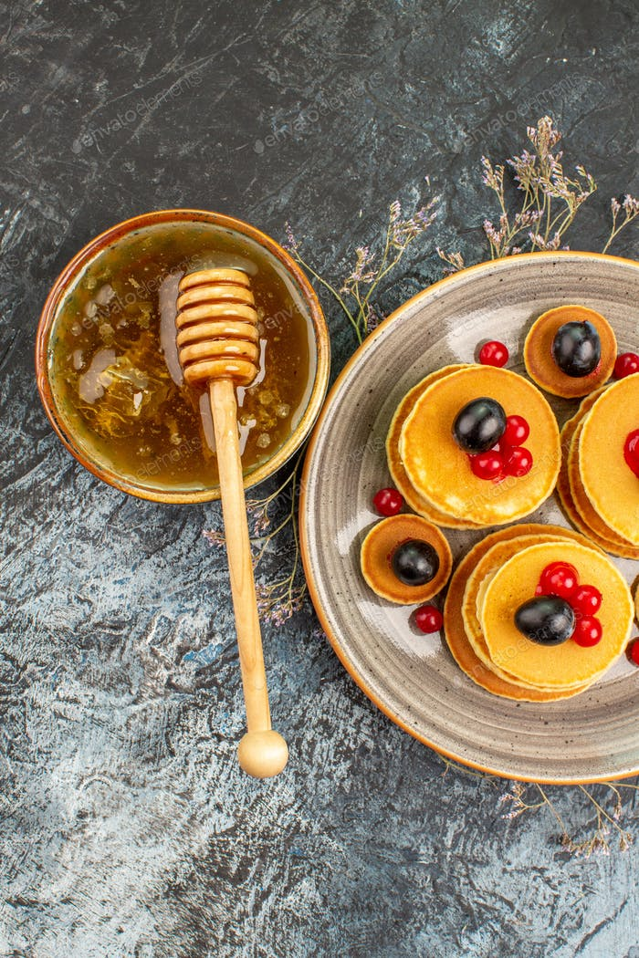 Vertical view of sweet honey with wooden spoon and pancakes