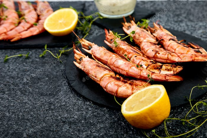 Grilled big tiger shrimps prawns on black slate plate