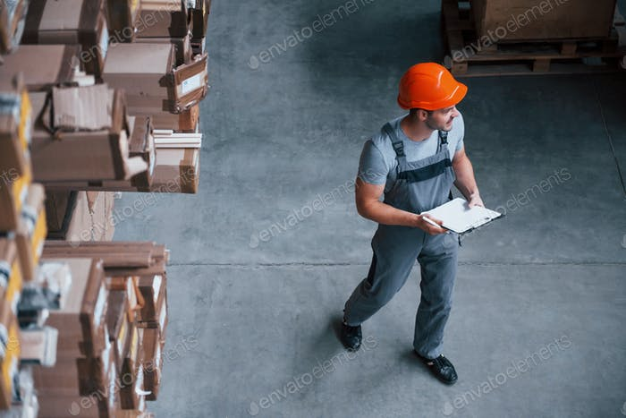Top view of male worker in warehouse with notepad in hands