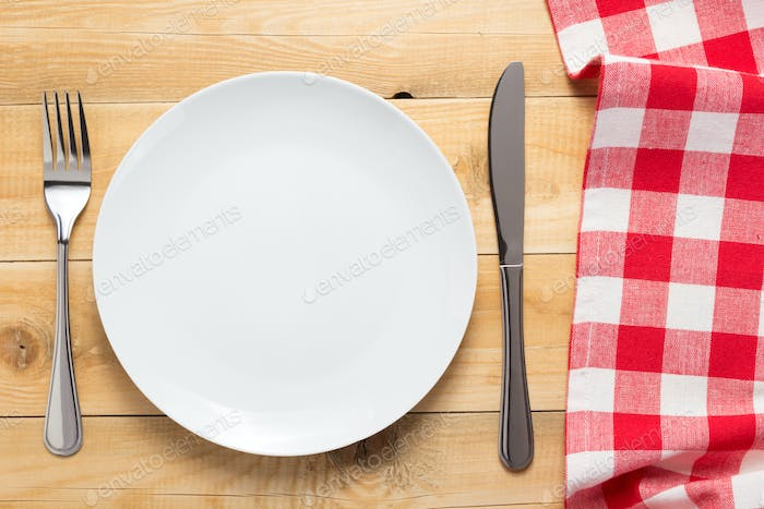 plate, knife and fork at wooden  table background