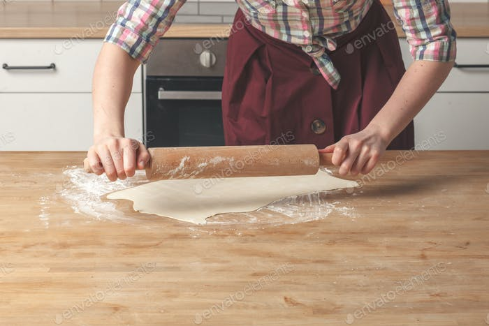 female housewife baker hands cooking pastry with rustic rolling pin