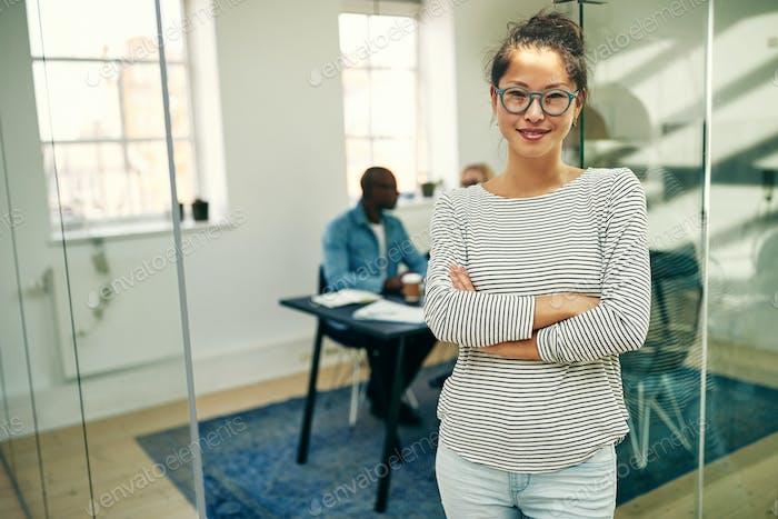 Selbstbewusste junge asiatische Geschäftsfrau stehend in einem modernen Büro