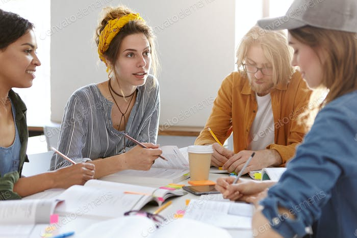 University, college, teamwork concept. Thrree college females and one bearded guy sitting at desk wi