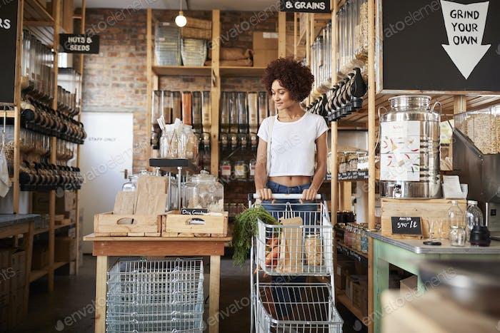 Frau mit Einkaufswagen kaufen frisches Obst und Gemüse in Kunststoff Free Lebensmittelgeschäft