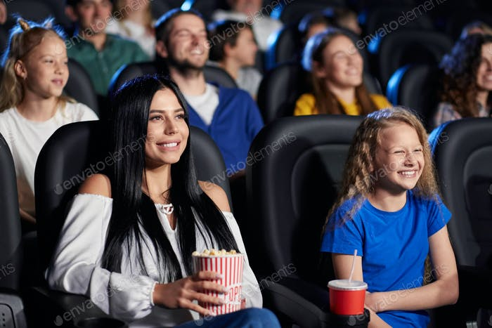Brunette woman with younger sister in cinema