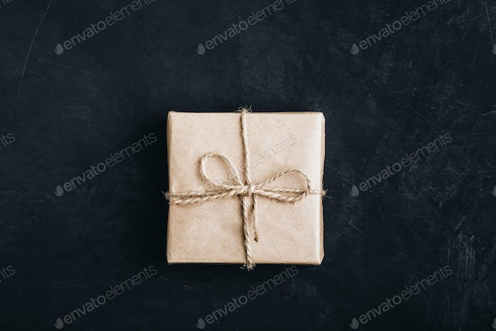 Christmas gift box. Christmas present in paper box on dark stone background. Top view